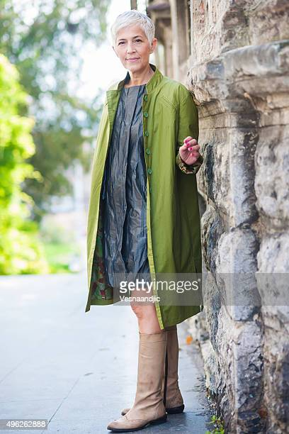 mature woman - green coat stock pictures, royalty-free photos & images