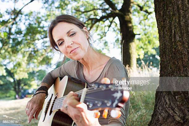 Mature woman playing acoustic guitar in park
