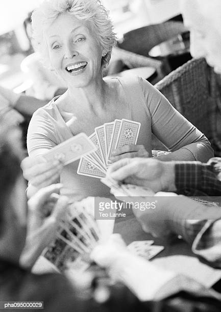 Mature woman playing cards, blurred foreground, B&W