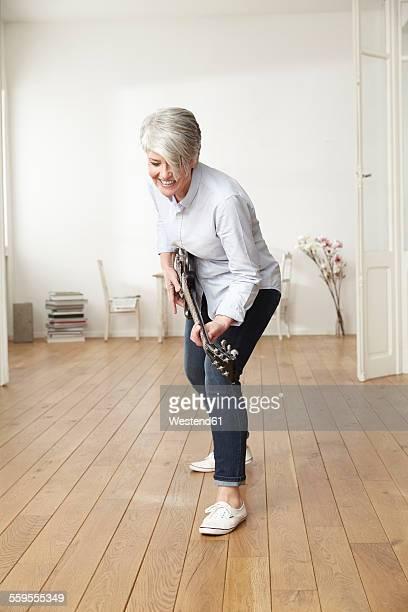 Mature woman playing electric guitar