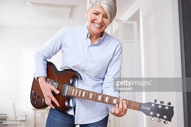 Mature woman playing electric guitar