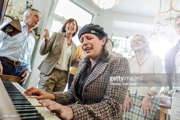 Ältere Frau spielt Klavier, während Freund hören