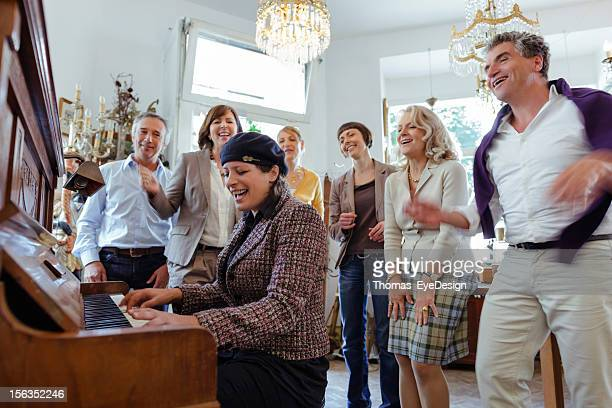 mature woman playing piano while friend listen - pianist front stock pictures, royalty-free photos & images