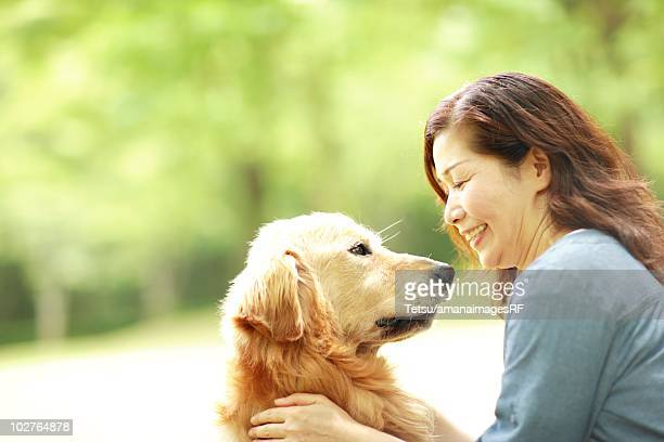 mature woman playing with her dog in her back yard - ゴールデンレトリバー ストックフォトと画像