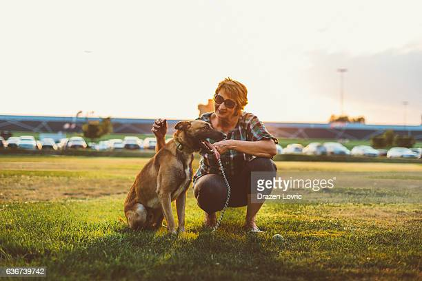 Mature woman playing with her Malinois dog