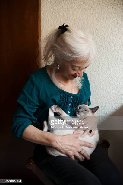 A mature woman plays with a kitten