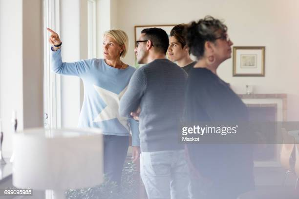 Mature woman pointing and showing to friends through window while standing in living room