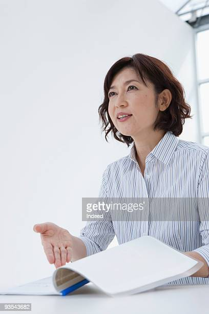 Mature woman pointing documents
