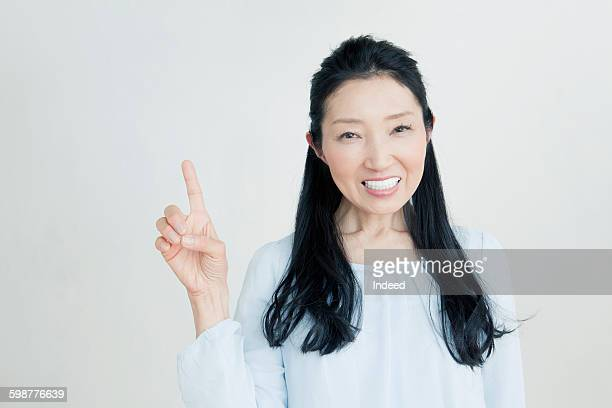 Mature woman pointing up