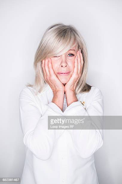 A mature woman posing in a studio looking perplexed