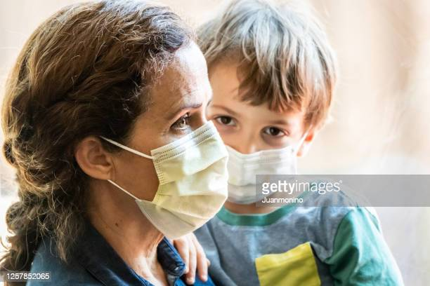 mature woman posing with her son, both with protective masks, very sad looking through window worried about covid-19 pandemic - uncertainty stock pictures, royalty-free photos & images