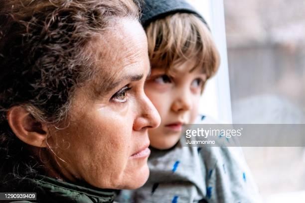 mogen kvinna poserar med sin son, mycket sorgligt tittar genom fönstret orolig förlust av sitt jobb på grund covid-19 pandemi - fattigdom bildbanksfoton och bilder