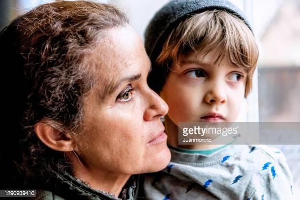 reife frau posiert mit ihrem sohn, sehr traurig blick durch das fenster besorgt über den verlust ihres jobs durch covid-19 pandemie - armut stock-fotos und bilder