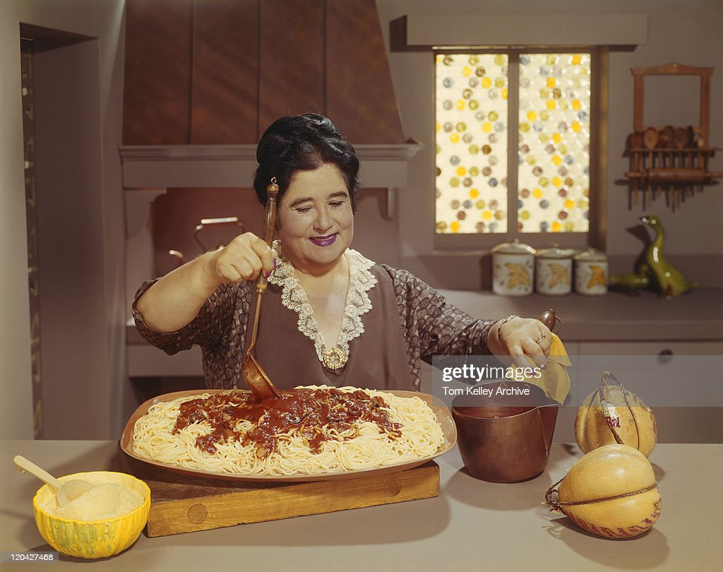 mature woman preparing pasta in traditional italian kitchen stock
