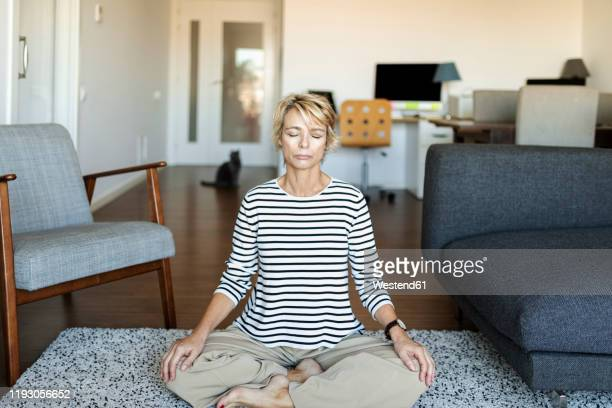 mature woman practicing yoga at home - mindfulness stock pictures, royalty-free photos & images