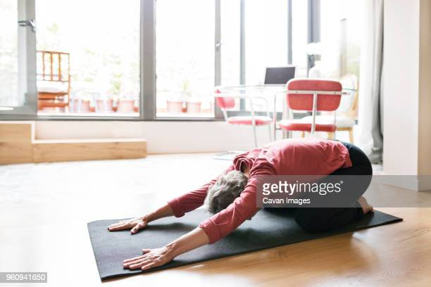mature woman practicing yoga in childs pose at home - childs pose stock photos and pictures