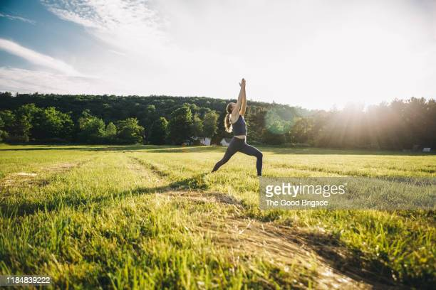 mature woman practicing yoga in field - zen like stock pictures, royalty-free photos & images