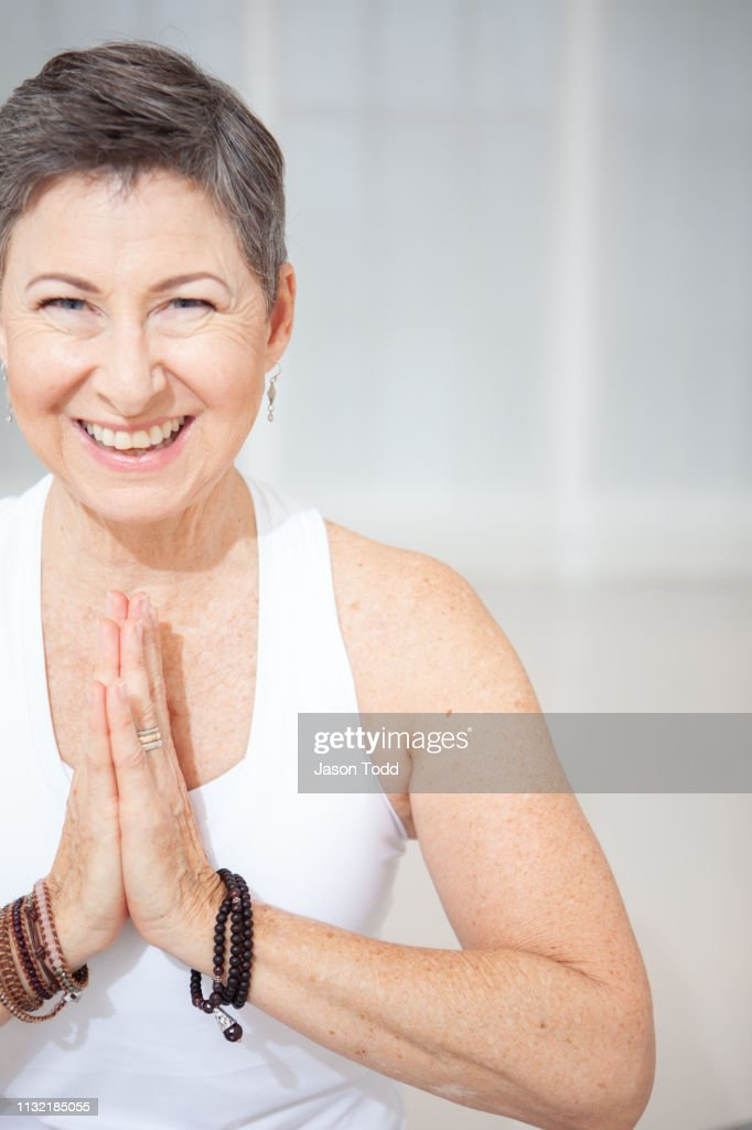 mature woman practicing yoga in namaste pose smiling : Stock Photo