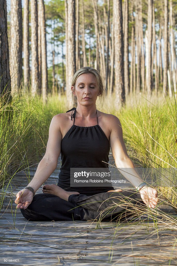 Young Woman Enjoying Meditation And Yoga On Green Grass In