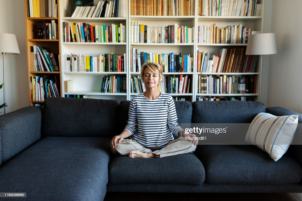 Mature woman practicing yoga on couch at home : Stock Photo