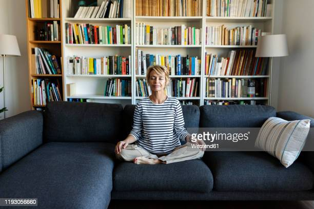 mature woman practicing yoga on couch at home - spiritualiteit stockfoto's en -beelden