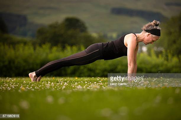 Mature woman practicing yoga plank in field