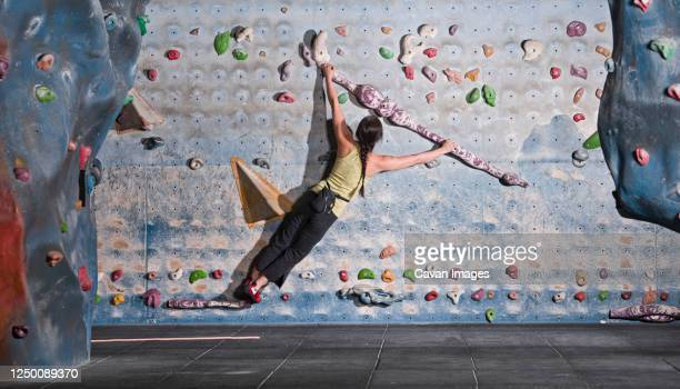 mature woman practising at indoor climbing wall in the uk - individual event stock pictures, royalty-free photos & images