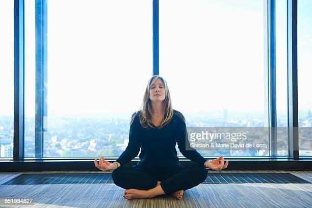 Mature woman practising yoga in room
