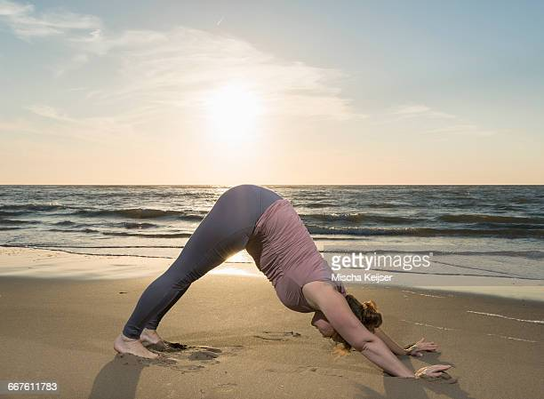 mature woman practising yoga on a beach at sunset, downward facing dog pose - fat lady in leggings stock photos and pictures