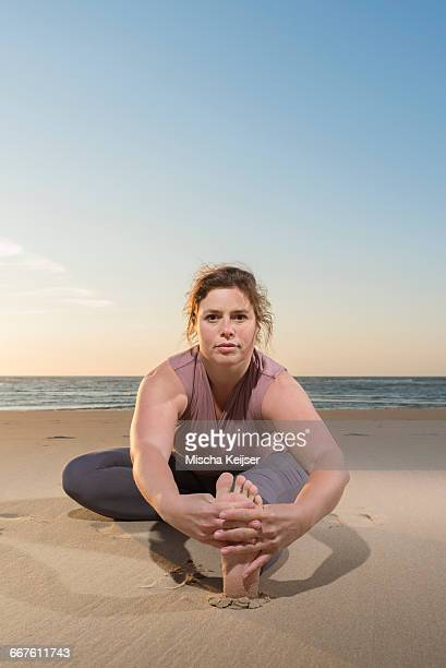mature woman practising yoga on a beach at sunset, portrait touching toes - fat lady in leggings stock photos and pictures