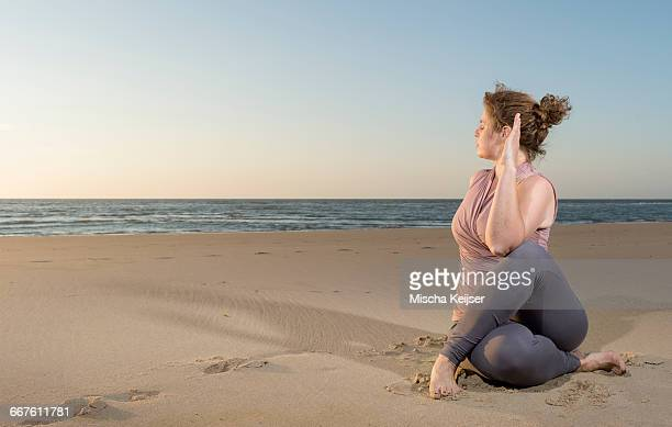 mature woman practising yoga on a beach at sunset, sitting cross legged - fat lady in leggings stock photos and pictures