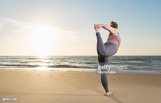 mature woman practising yoga on a beach at sunset, tree pose - fat lady in leggings stock photos and pictures