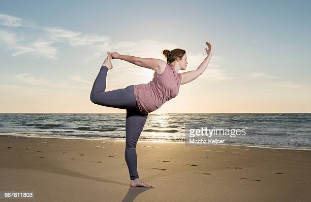 Mature woman practising yoga on a beach at sunset, tree pose