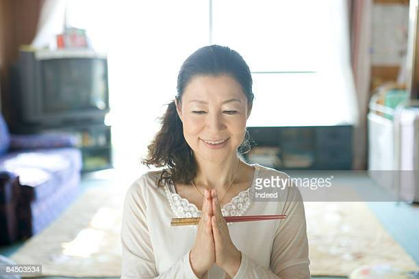 Mature woman praying before meal