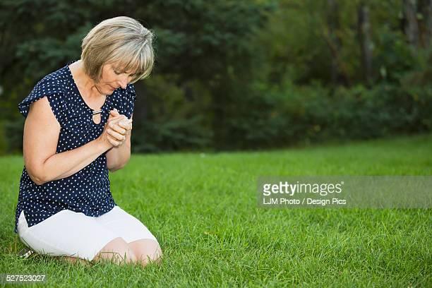 mature woman praying in the park - mulher orando de joelhos imagens e fotografias de stock