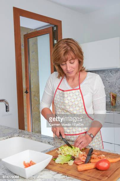 Mature Woman Preparing Salad In Kitchen At Home