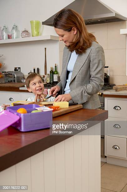 Mature woman preparing sandwiches in kitchen looking at son (4-6)