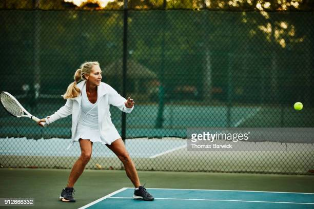 Mature woman preparing to hit return while warming up for early morning tennis match