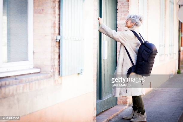 Mature woman pressing front door bell in local french village