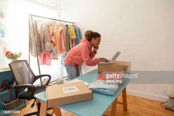 mature woman processing an order from an office in her home - e commerce stock pictures, royalty-free photos & images