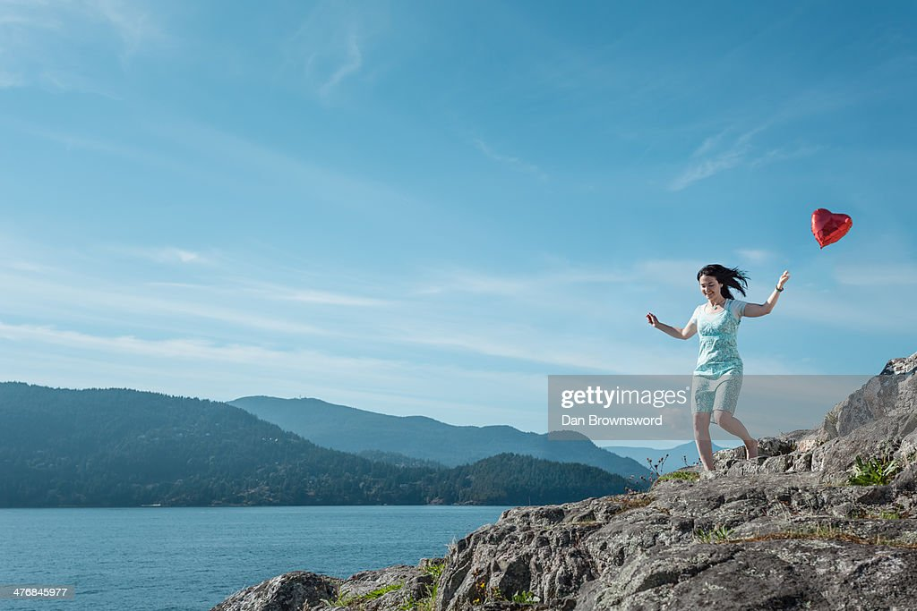 Mature woman pulling heart shaped balloon, Vancouver, Canada : Stock Photo