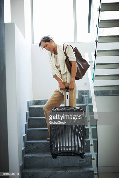 mature woman pulling her heavy luggage up the stairs - struggle stock pictures, royalty-free photos & images