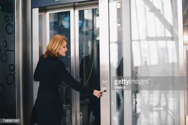 Mature woman pushing button of elevator at railroad station