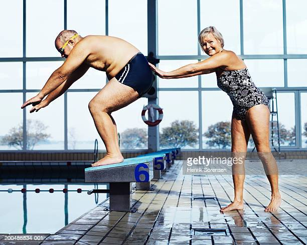 Mature woman pushing man on diving board in swimming pool, smiling
