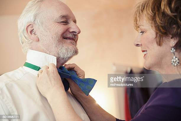 Mature woman putting bow tie on senior man