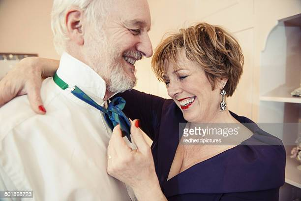 Mature woman putting bow tie on senior man
