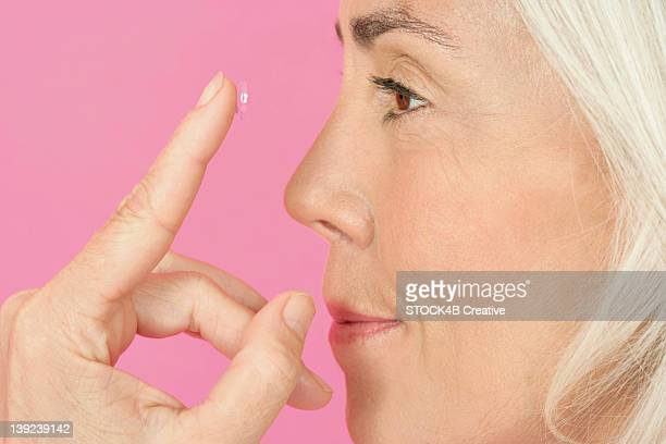 Mature woman putting contact lenses in
