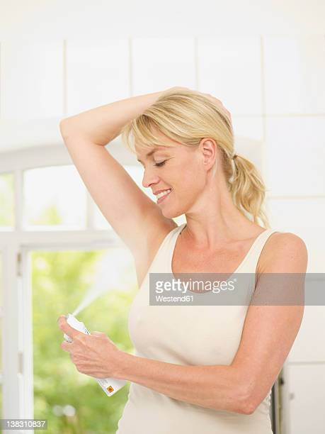 Mature woman putting deodorant on underarms, smiling