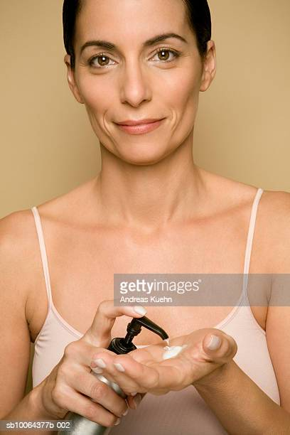 Mature woman putting lotion on hand, portrait, close-up