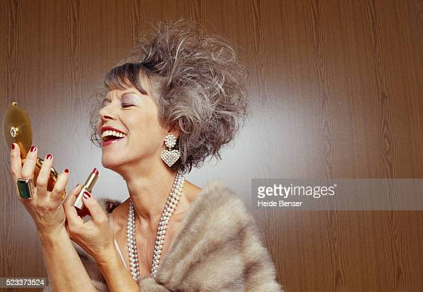 mature woman putting on make-up - fur coat stock pictures, royalty-free photos & images